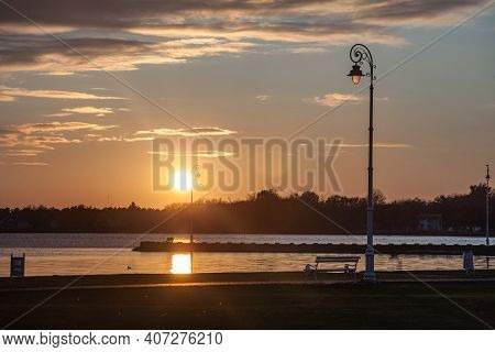 Public Bench And Streetlamp In Front Of  Palic Lake In Subotica, Serbia, With A Green Lawn In The Fo
