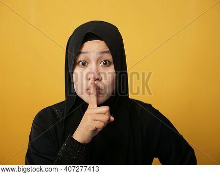 Portrait Of Asian Muslim Lady Wearing Hijab Shushing Gesture, Put Her Finger On Lips Telling Secretl