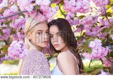 Spring Girls Fashion. Beautiful Young Woman Enjoying Flowering Garden. Girlfriends Couple