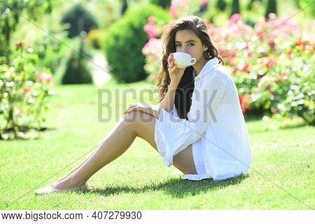 Spring Woman With Coffee Outdoor. Happy Girl Outdoors In Rose Garden. Woman Enjoy Outdoor Recreation