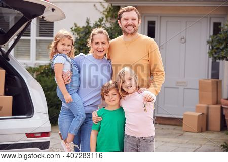Portrait Of Family Outside New Home On Moving Day Unloading Boxes From Car