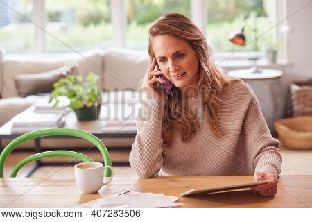 Smiling Woman On Phone Call Sitting At Table At Home With Digital Tablet Reviewing Domestic Finances