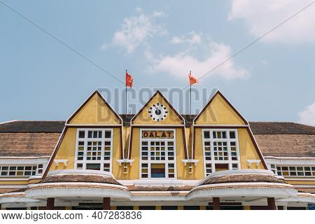 Old Yellow Train Station Sign With Clock And Flags In Dalat, Vietnam.