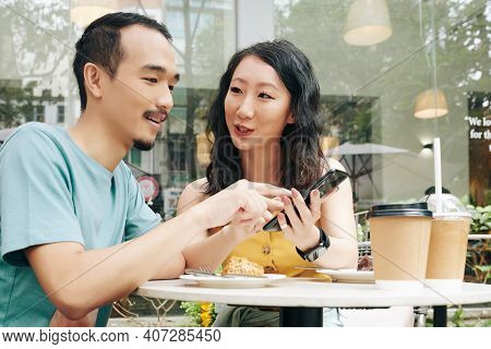 Young Chinese Couple Discussing Posts Or Photos On Social Media When Enjoying Romantic Date In Outdo