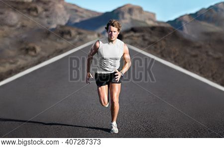 Sport athlete runner man running training endurance on mountain road sprinting fast towards camera. Sprinter exercising for marathon. Young male fitness model on run outdoor in banner landscape.