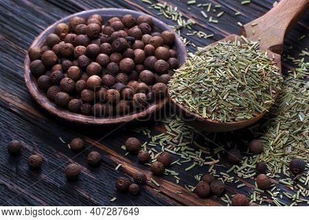 Dry Rosemary In A Wooden Spoon And Allspice On The Table