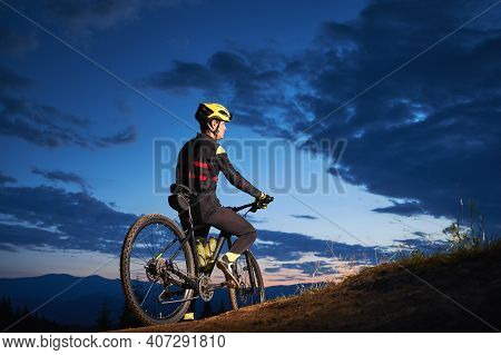 Back View Of Young Man In Cycling Suit Sitting On Bicycle Under Blue Night Sky With Clouds. Male Bic