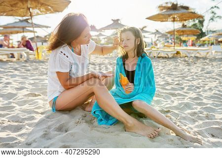 Mom And Preteen Daughter On The Beach Together, Mother Putting On Kids Face Sunscreen, Caring Love C