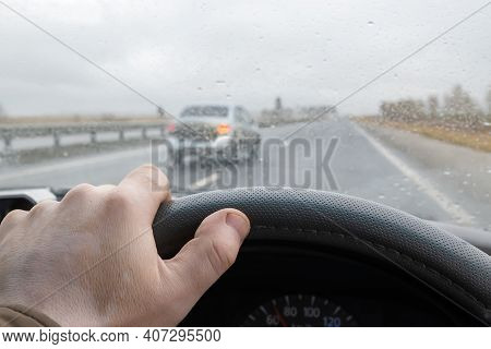 View Of The Driver Hand On The Steering Wheel Of A Car That Is Driving On The Highway And In Front O