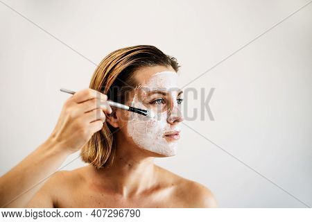 A Beautiful Woman Applies A White Mask To Her Face, Takes Care Of Beauty. The Concept Of Self-care,