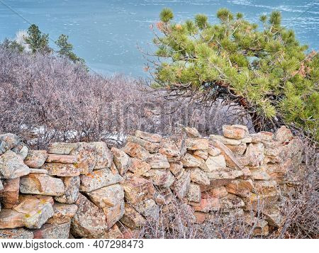 old stone fence at foothills of Rocky Mountains above Horsetooth Reservoir - a popular recreational area in northern Colorado, fall or winter scenry with a low water level