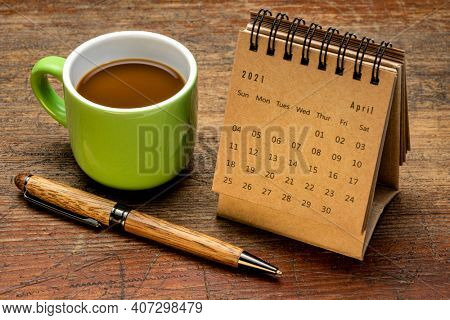 April 2021 - spiral desktop calendar against rustic weathered wood, time and business concept