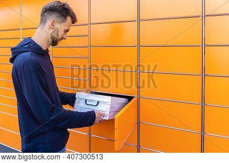 Guy Holding Parcel And Sending Using Yellow Self-service Post Terminal Machine. Man Sends Shipment U