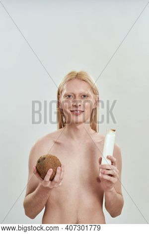 Happy Young Caucasian Man With Long Blond Hair Holding Shampoo Bottle And Coconut In Hand While Stan