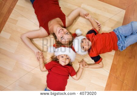 Woman And Her Kids On The Floor At Christmas