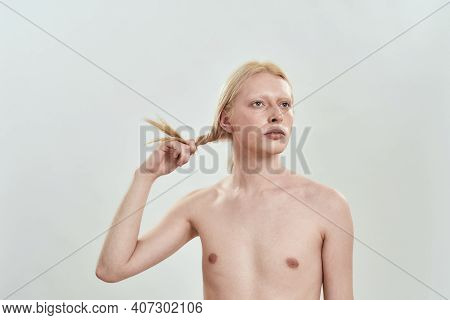 Young Caucasian Man Holding His Long Blond Hair In Hand While Standing On White Background And Looki