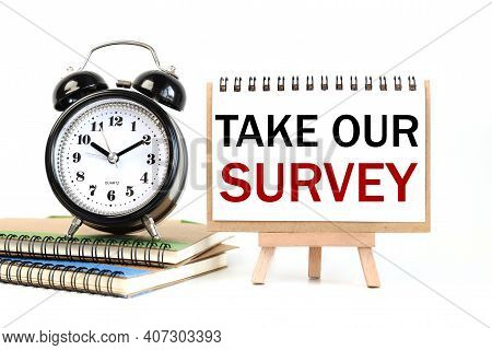 Take Our Survey. Text On White Notepad Paper On A Stand Next To Our Desk Clock On A Sideboard. On Wh