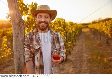 Happy Bearded Winemaker With Glass Of Wine Leaning On Fence And Smiling For Camera On Grape Farm At