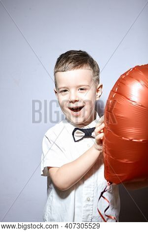 Valentine\'s Day. Happy Boy Stands And Holds Red Ball Hearts On A White Background.