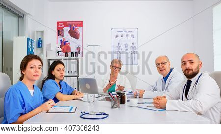Group Of Specialist Doctors Having Video Meeting, Discussing On Webcam Sitting At Desk In Medical Co
