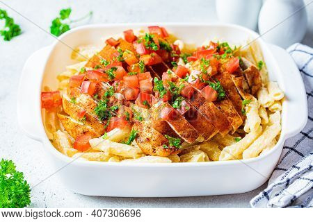 Cajun Chicken Pasta With Cheese And Tomato In White Dish.