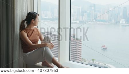 Young woman look at the city view at hotel room