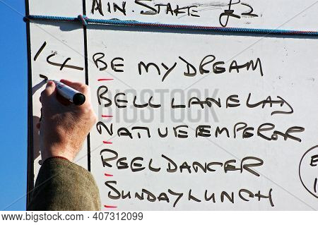 A Bookmaker Writing Up The Odds For A Point To Pointhorse Race On A Sunny Winter Day.