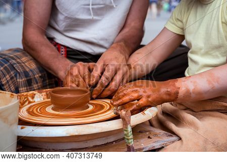 The Potter Teaches The Pottery Craft. Making Pottery On A Potter's Wheel. Hands Close-up.