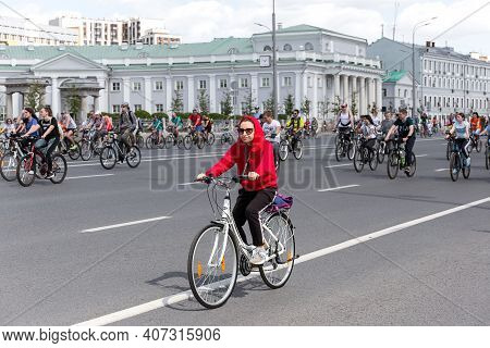 Moscow, Russia, May 19, 2019: A Young Woman In A Red Jacket Rides A Bicycle On A Street In The City