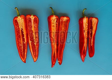 Three Pairs Of Red Salad Peppers In Two Halves Lie On A Blue Table Background. Summer Season.