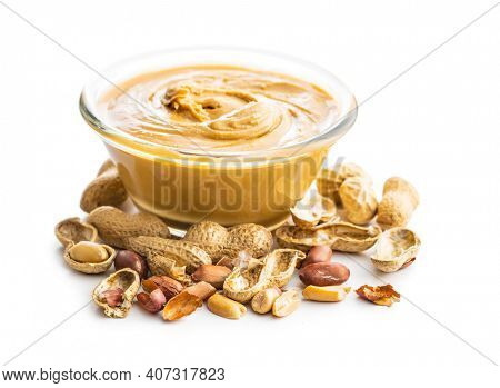 Peanut butter in bowl and peanuts isolated on white background.