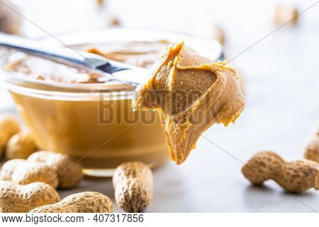 Peanut butter on knife and peanuts