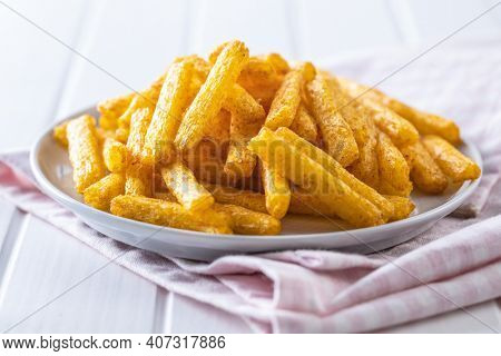 French fries. Salted snack. Potato chips on plate.