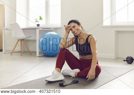 Happy Woman Resting After Successful And Active Fitness Workout Sitting On Sports Mat In Room.