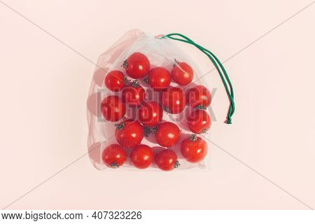 Reusable Packaging Of Products By Weight. Red Tomatoes In A Reusable Bag Close Up On A Pink Backgrou