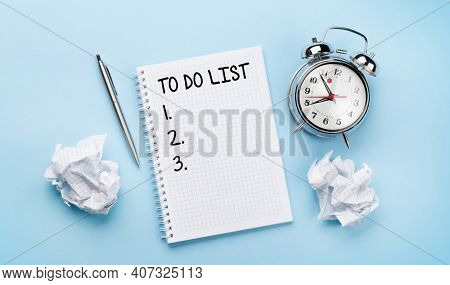 Office desk with supplies, alarm clock and to do list notepad over blue. Creativity and inspiration work concept. Top view flat lay with copy space