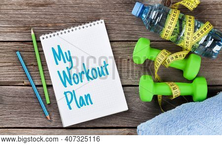 Diet and fitness concept. Dumbbells, water, tape measure and notepad with workout plan