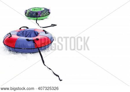 Two Snow Tubing For Active Winter Holidays. Games For Children's Holidays And Weekends. Copy Space.