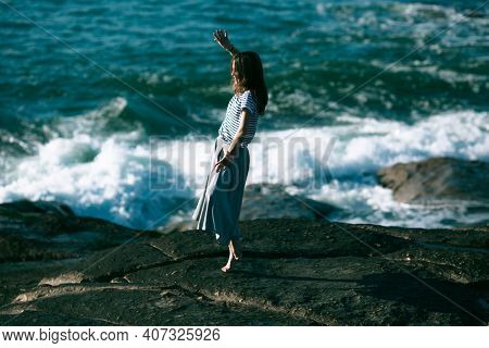 The dancer woman is engaged in choreography on the rocky coast of the Atlantic ocean.