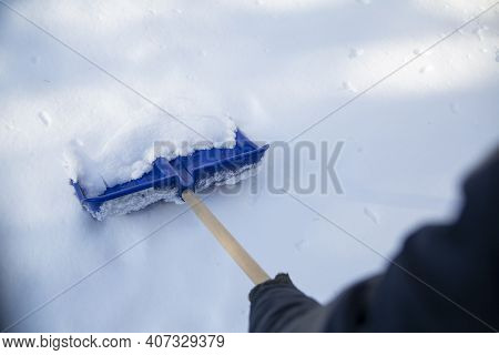Winter Household Chores. Shoveling Snow From A Sidewalk With A Snow Shovel, Top View.