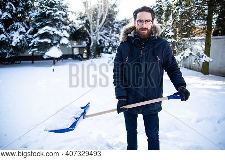 Man Shoveling Snow From A Sidewalk, A Driveway With A Snow Shovel.