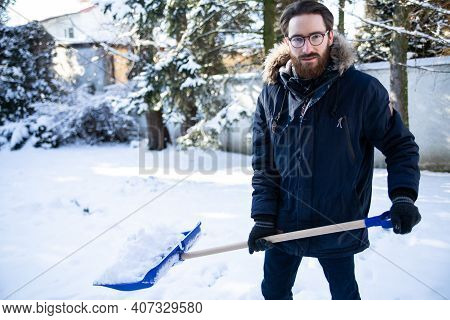 Shoveling Snow From A Sidewalk, A Driveway With A Snow Shovel.