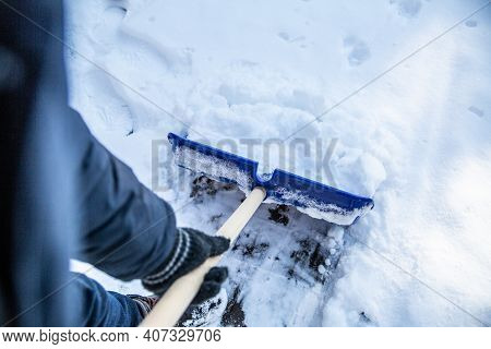 Shoveling Snow From A Sidewalk With A Snow Shovel, Top View.