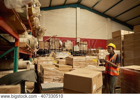 African Female Warehouse Worker Checking Inventory With A Digital Tablet