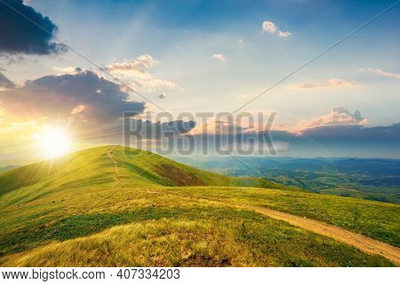 Mountain Landscape On A Bright Spring Sunset. Path Through Meadow In Grass On The Hill In Evening Li