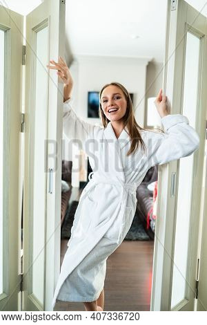 Young And Joyful Woman In Bathrobe Standding Near A Glass Doors At Home
