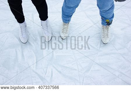 Close-up Of Female Feet Ice Skating In Winter On An Outdoor Ice Rink. Ice Skates Of Two Friends Ice