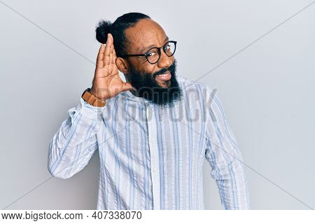 Young african american man wearing business style smiling with hand over ear listening and hearing to rumor or gossip. deafness concept.
