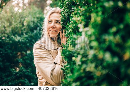 Portrait Of Blonde Smiling Woman In Green Forestor Park In Summer Wearing Trendy Beige Trench Coat