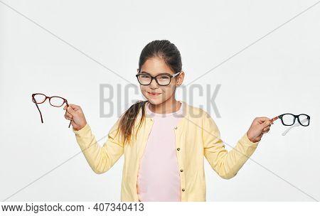 Cute Asian Girl Wearing Glasses Holding Stylish Eyeglasses. Vision Correction With Childs Eyeglasses